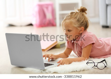 Little girl with laptop in the room - stock photo