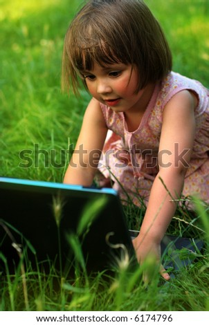 little girl with laptop on grass background - stock photo