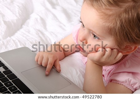 Little girl with laptop on the bed - stock photo