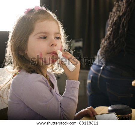 little girl with lipstick - stock photo