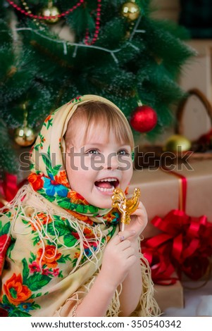 little girl with Lollipop at the Christmas tree Russian style - stock photo