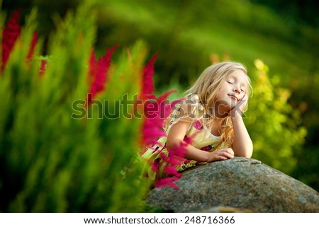 little girl with long blond hair in the garden - stock photo