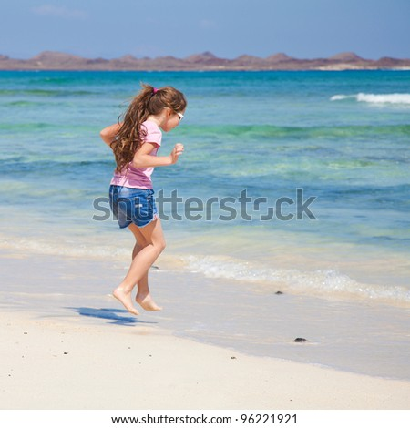 little girl with long brown hair in ponytail in pink t-shirt and denim shorts by the ocean - stock photo