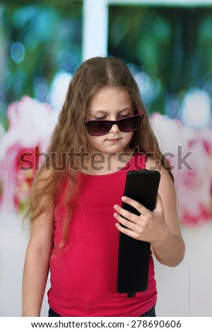 Little girl with long hair and big sunglasses looks to classy smartphone in her hands - communication and modern technology concept