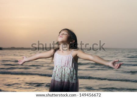 Little girl with long hair dressed and have open arms and eyes closed to the shore of a beach - stock photo