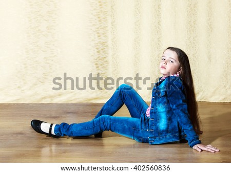 little girl with long hair in a blue denim suit posing while sitting on the floor in the studio
