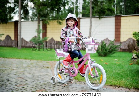 Little girl with long hair in colorful dress sits on the fur on funny tree background - stock photo