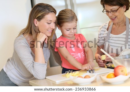 Little girl with mom and grandmother baking cookies at home - stock photo
