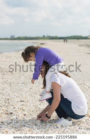 Little girl with mom playing with shells on the beach. Mother and daughter enjoying summer. Family affair. Mom and little girl having fun on the beach.  - stock photo