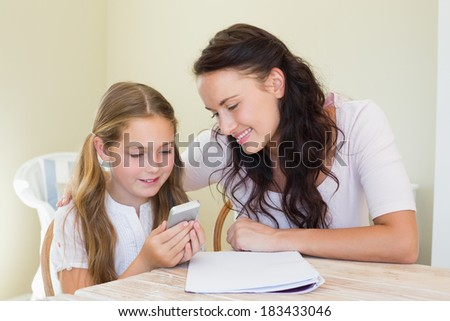 Little girl with mother using cell phone at table in house - stock photo