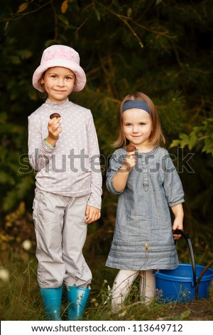 little girl with mushrooms in the forest - stock photo