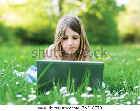 LIttle girl with notebook computer on green meadow - stock photo
