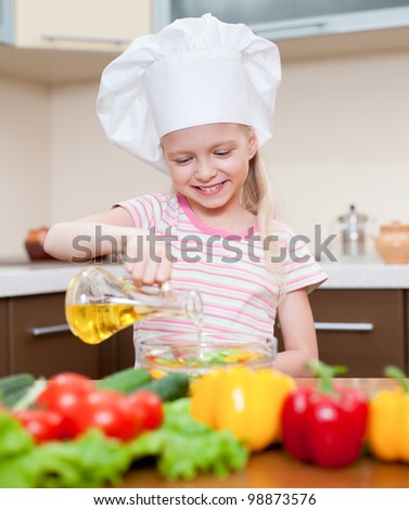 Little girl with oil preparing healthy food on kitchen - stock photo