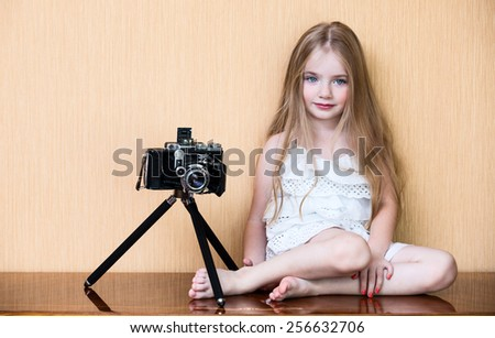 Little girl with oldest camera - stock photo