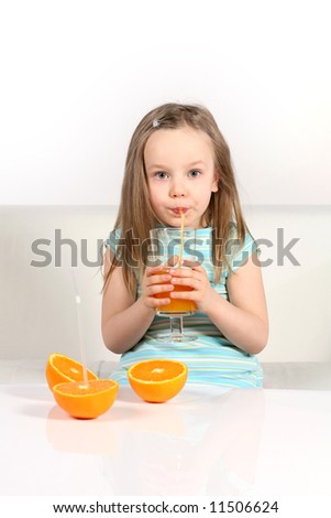Little girl with oranges and juice on white sofa and background.