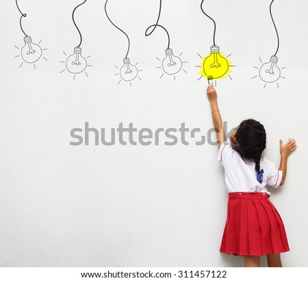 little girl with paintbrush creative drawing light bulb ideas on wall, back view - stock photo