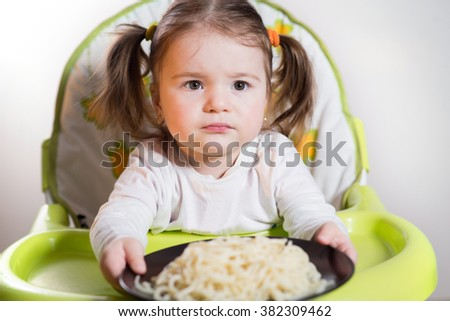 little girl with pasta sitting in the baby chair at home