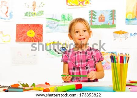 Little girl with pencil in the art development class in kindergarten  - stock photo