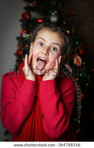 little girl with pigtails in red knitted sweater against the backdrop of the Christmas tree, dark background