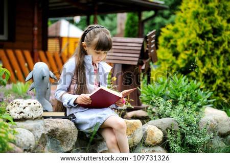 Little girl with pink backpack reading a book outdoors - stock photo