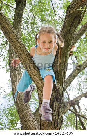 little girl with plaits is climbing on a tree - stock photo