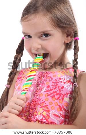 little girl with plaits sucking lollipop - stock photo