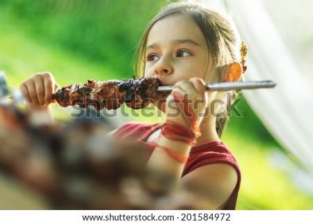 Little girl with pleasure eats shish kebab - stock photo