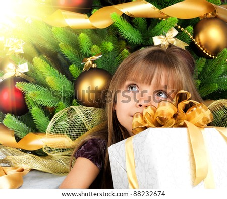 little girl with present near the Christmas tree - stock photo