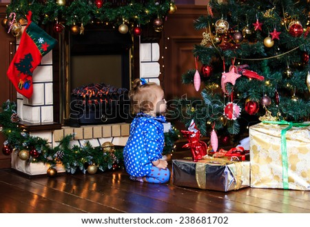 little girl with presents at christmas home