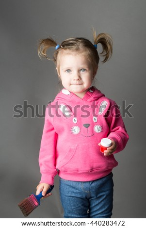 Little girl with pretty face and funny hairstyle holding paint and brush in studio on grey background - stock photo