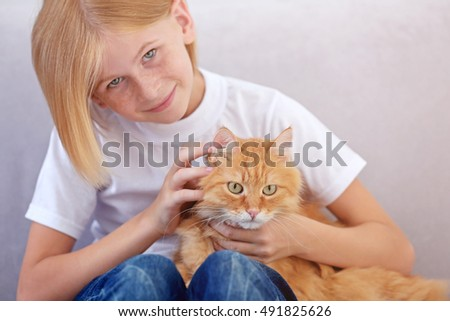 Little girl with red fluffy cat on sofa in room