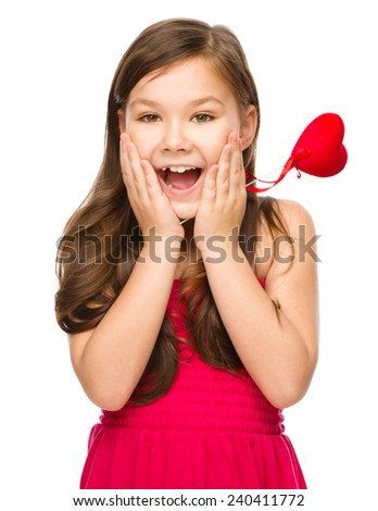 Little girl with red heart, holding her face in astonishment, Valentine concept, isolated over white - stock photo