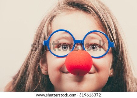 Little girl with red nose. Prepare to have fun, carnival time - stock photo