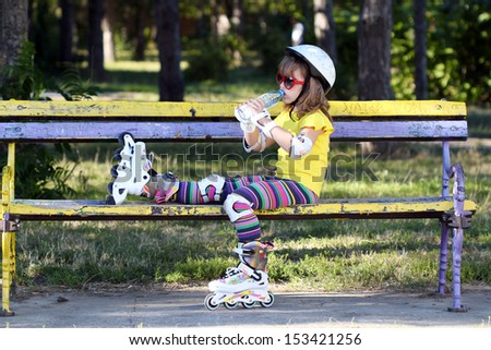 little girl with roller skates sitting on bench and drink water  - stock photo