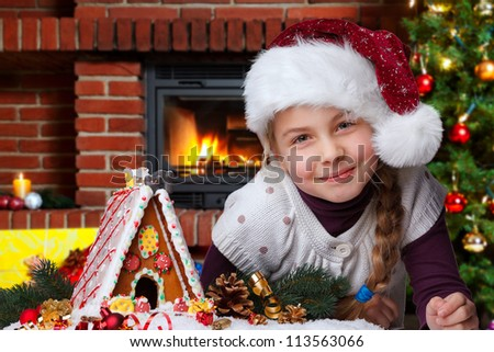 little girl with santa hat and gingerbread house - stock photo