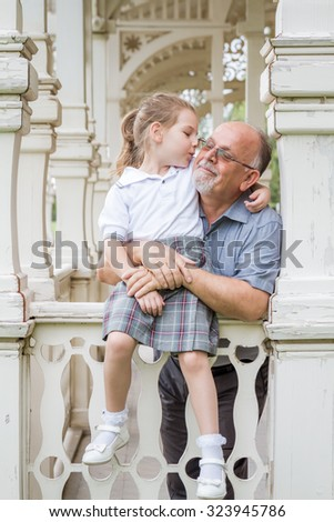 Little girl with school uniform and her grandfather in green park - stock photo