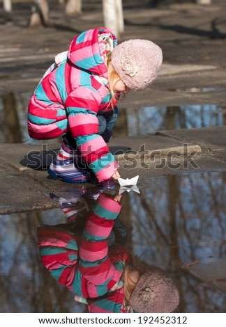 little girl with ship at the spring time  - stock photo