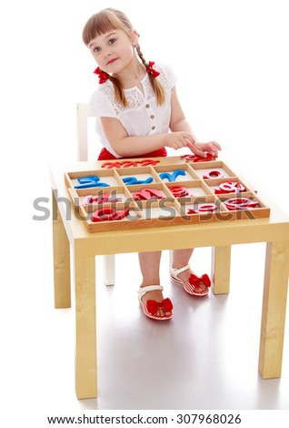 little girl with short bangs and thin hair on his head sitting at a table in a Montessori kindergarten. Girl to learn the alphabet-Isolated on white background - stock photo