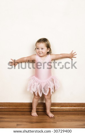 Little girl with short hair wearing a pink ballet outfit