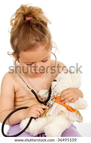 Little girl with small pox playing doctors with her teddy bear - isolated healthcare concept - stock photo