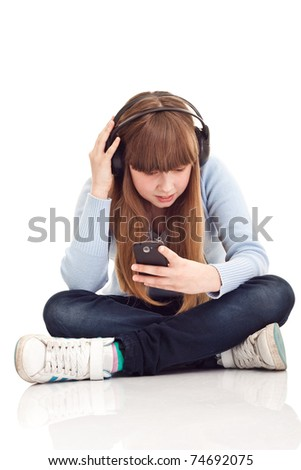 little girl with smartphone listening music, on white background - stock photo