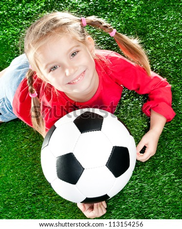 little girl with soccer ball  on a green lawn