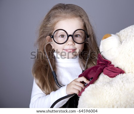 Little girl with  stethoscope and bear cub. Studio shot. - stock photo