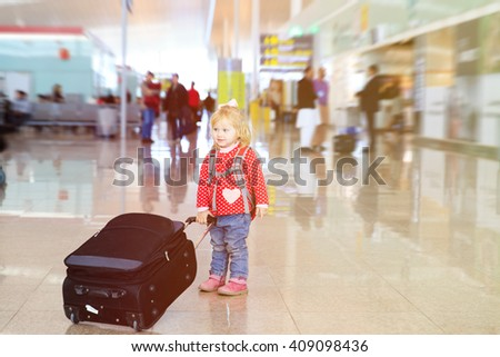 little girl with suitcase travel in the airport - stock photo