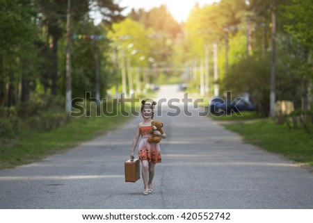 Little girl with suitcase walking along the road. - stock photo