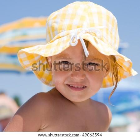 Little girl with sun hat on beach - stock photo