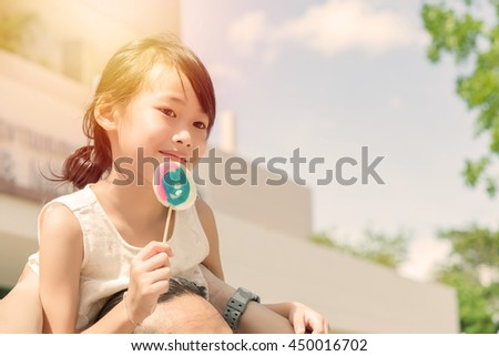 Little girl with sweet candy from low angle vintage style,bright sunlight - stock photo