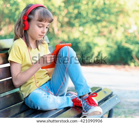 Little girl with tablet pc and headphones sitting on the bench and listening to music or watching video in summer park