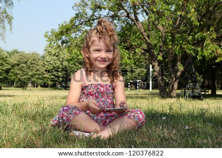 little girl with tablet pc in park - stock photo