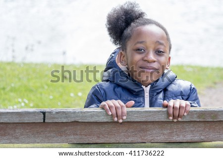 Little girl with tears in her eyes on a park bench - stock photo